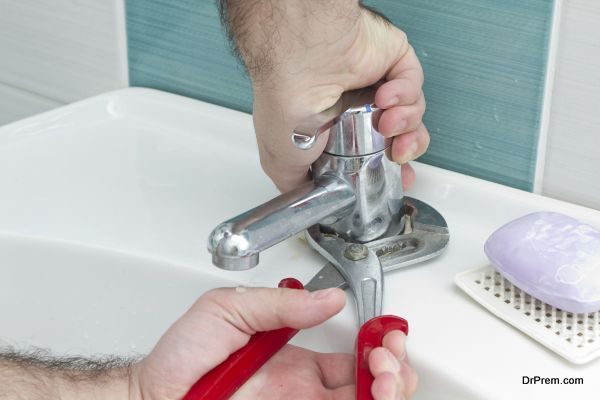 Plumber hands tightning water outlet with pliers
